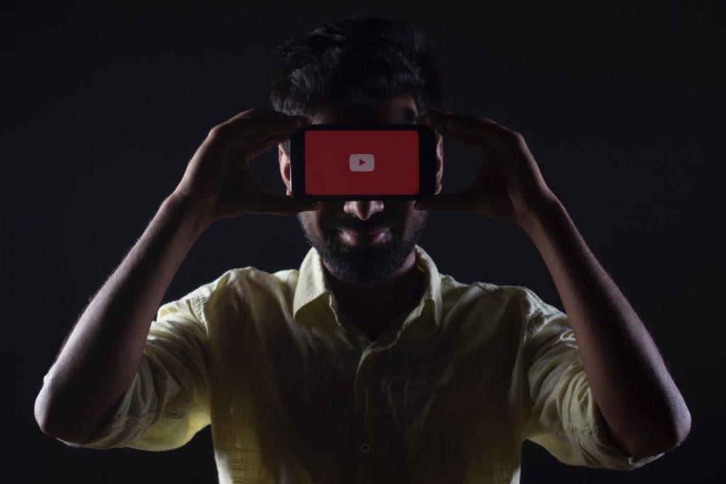 Un homme tient un téléphone devant ses yeux sur lequel le logo de Youtube apparait.