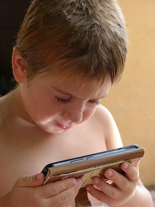 Une petit garçon qui regarde au téléphone pour expiquer